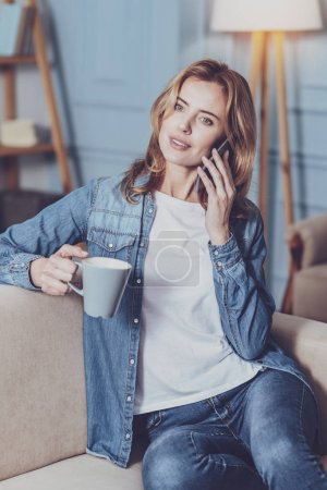 Positive delighted female person talking per telephone