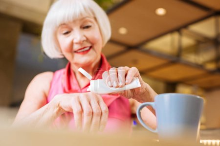 Cheerful senior woman caring about her skin