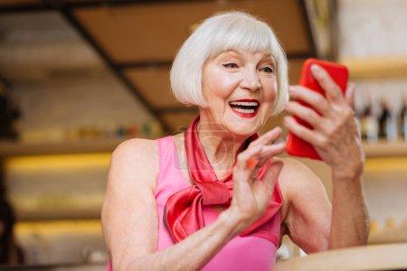 Photo pour Nouveau message. Femme heureuse positive regardant l'écran du smartphone tout en recevant un nouveau message - image libre de droit