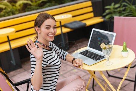 Smiling businesswoman wearing striped shirt waving her friend