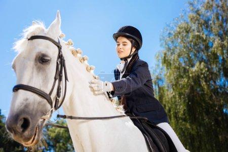 Photo pour Une cavalière aimante. Aimant sculpture belle femme de cheval caressant son doux cheval de course blanc - image libre de droit