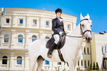 Photo pour Sur la piste de course. Élégante femme douce port équitation bottes équitation son cheval blanc sur la voie de la grande course - image libre de droit