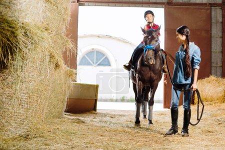 Horsewoman teaching her daughter riding racing horse