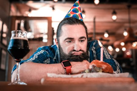 Photo for No appetite. Mature birthday man having no appetite looking at his food while spending evening al by himself - Royalty Free Image