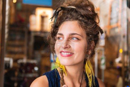 Beaming woman. Beautiful beaming woman wearing bright yellow earrings smiling broadly feeling happy