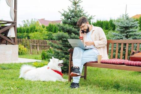 Foto de Contestar llamada. Independiente ocupado contestando llamada mientras trabaja fuera de su casa de verano junto a su perro - Imagen libre de derechos
