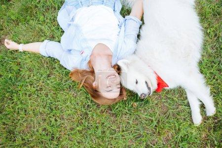 Lächelnde blondhaarige Frau, die mit ihrem weißen Hund im Gras liegt
