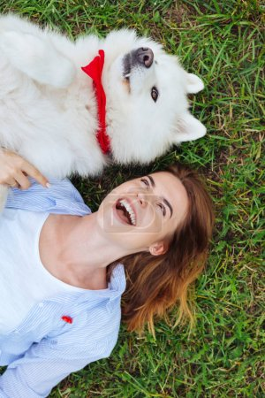 Stylish woman feeling happy while meeting her white dog