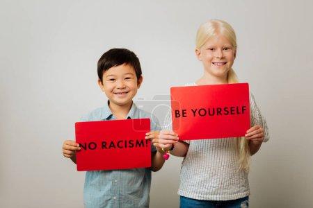 Kluge Kinder mit Tischen gegen Rassismus in der Hand