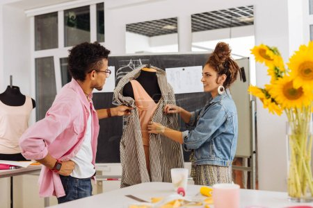 Friendly dressmakers working at the new fashionable dress together
