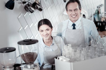 Positive baristas smiling and standing near the coffee machine