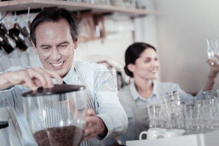 Mature barista smiling while making coffee