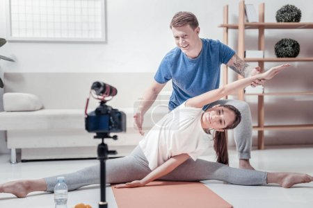 Smiling man helping woman doing exercises