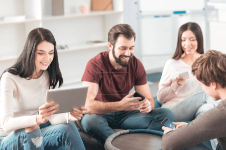 Photo for Digital generation. Joyful young people sitting in the circle while using their gadgets - Royalty Free Image