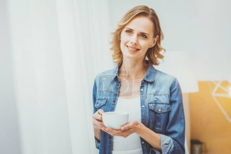 Relaxed young woman holding cup in both hands