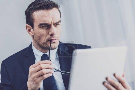 Foto de Mindfulness. Pensativo empresario serio sosteniendo gafas y mirando atentamente a la pantalla de la tableta en sus manos mientras tiene mirada pensativa - Imagen libre de derechos