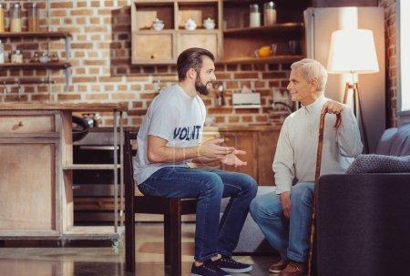Photo pour Parle-moi. Sympathique agréable séance de bénévolat inébranlable sur la chaise en gesticulant et en communiquant avec un retraité. - image libre de droit