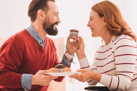 Overjoyed couple eating cupcakes