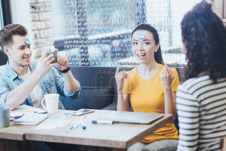 Photo pour Toujours amusant. Trois amis agréables jouer au jeu tandis que l'homme enregistrement vidéo - image libre de droit