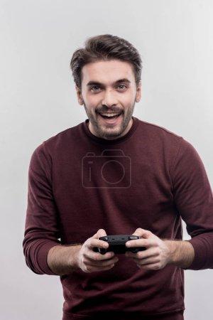 Foto de Hombre con joystick. Hombre joven guapo emocional con joystick mientras disfruta de juegos de video en la imagen sin retoque de cara - Imagen libre de derechos