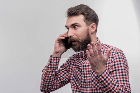 Phone conversation. Image without face retouching with bearded dark-haired man feeling angry while having phone conversation