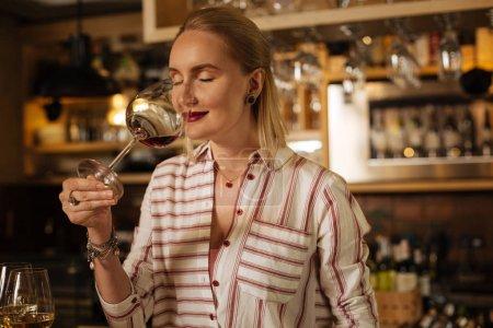 Delighted joyful female sommelier checking the wine smell