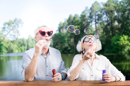 Grandfather and grandmother using soap bubbles of their grandchildren