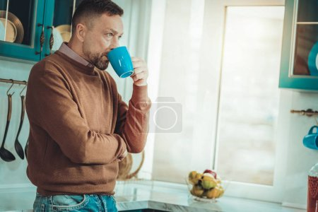 Thoughtful man drinking coffee in the kitchen
