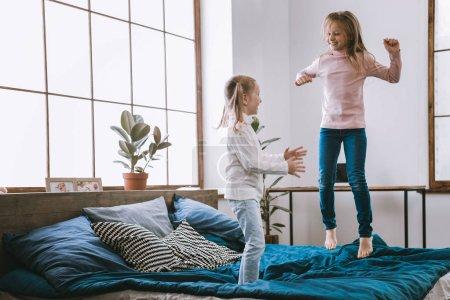 Joyful happy girls jumping on the bed