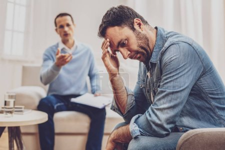 Unhappy depressed man holding his forehead