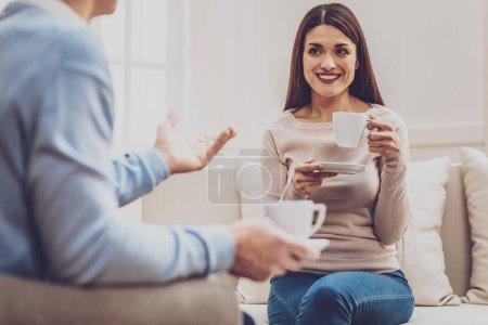 Photo pour Bonne humeur. Gai femme positive regardant son psychologue tout en prenant un café avec lui - image libre de droit