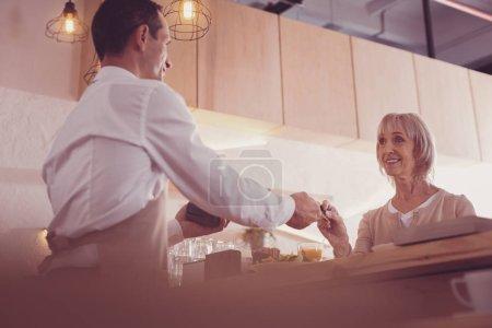 Photo pour Souriez et payez. Joyeux jolie femme âgée debout en face d'un homme souriant et tenant une carte de crédit . - image libre de droit