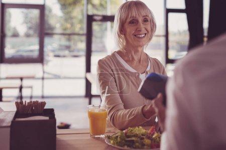 Photo pour Tout va bien. Satisfait femme agréable âgée debout dans le café regardant de côté et souriant . - image libre de droit