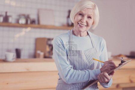 Photo pour J'attends votre ordre. Satisfait femme amicale âgée debout dans la pièce vide lumineuse souriant et tenant la tablette . - image libre de droit