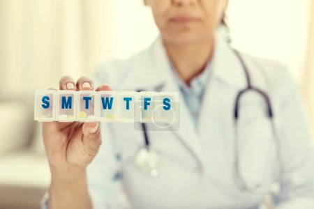 Photo for Easy and organized. Selective focus on a plastic medication box held by a mature medical professional showing the organizer into the camera. - Royalty Free Image