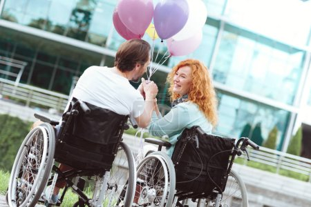 Charming husband and wife in wheelchairs beaming while holding balloons
