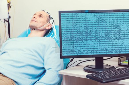 PC displaying brain waves of male patient at lab