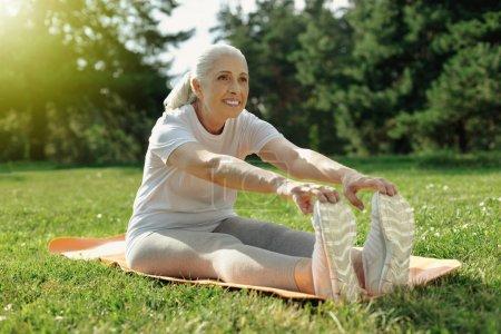 Joyful elderly lady stretching her back in park