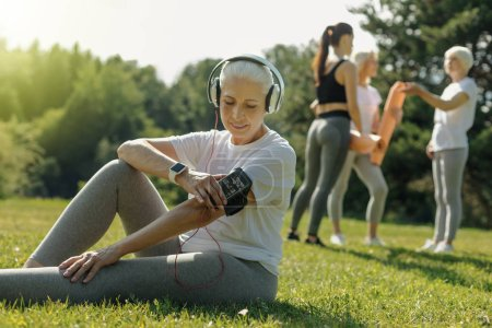 Relaxed senior lady turning music before workout