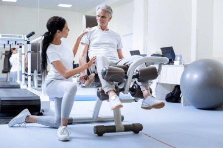 Photo pour Personne de confiance. Homme senior souriant avec le genou blessé assis sur un appareil d'exercice tout en un travailleur calm attentif d'un centre de remise en état, vérifier son état - image libre de droit
