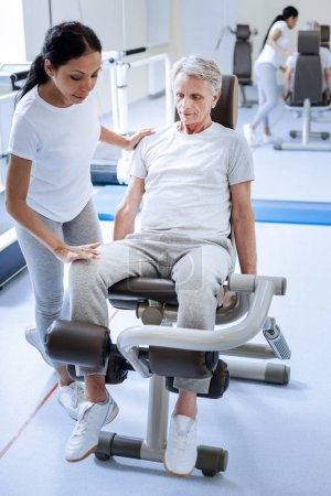 Serious concentrated injured man sitting on an exercise machine