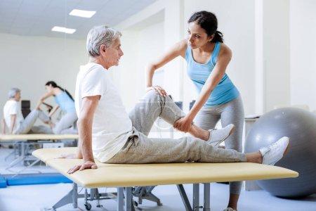 Aufmerksame Ärztin wärmt die verletzten Muskeln ihrer Patientin