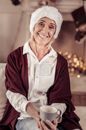 Photo pour Le meilleur jour de fête. Joyeux agréable femme amicale assise sur le canapé près de la cheminée tenant une tasse et souriant . - image libre de droit