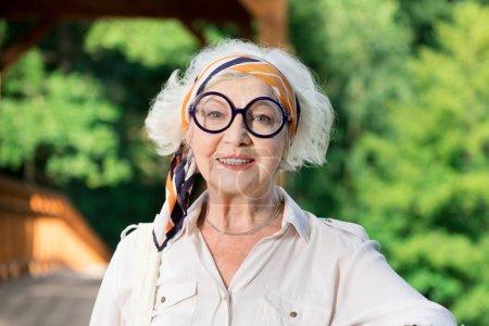 Photo pour Plutôt pensionné. Beau portrait de femme âgée gaie portant de grandes lunettes rondes et souriant gentiment - image libre de droit