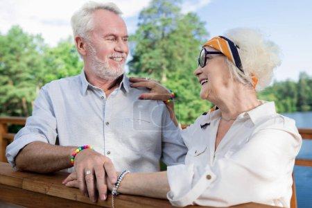 Photo pour Des retraités mignons. Assez heureux couple de personnes âgées souriant gentiment tout en se tenant sur le pont ensemble - image libre de droit