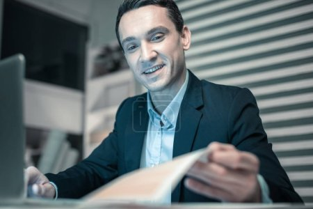 Photo for Busy people. Smiling smart business man watching at his notebook checking his schedule for the next week - Royalty Free Image