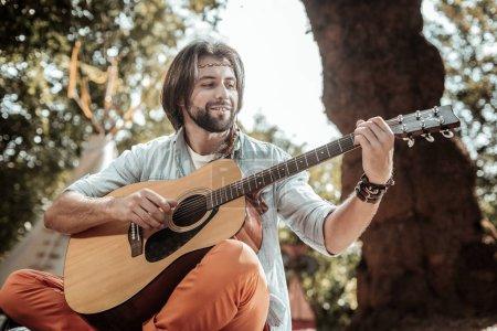 Foto de Canción feliz. Sonriente hombre con barba cantando canciones tocando guitarra descansa en la naturaleza - Imagen libre de derechos