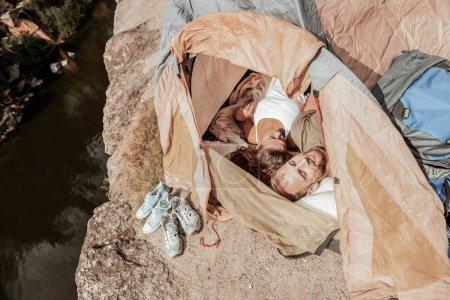 Femme bouclée aux cheveux foncés se sentant reposée tout en dormant dans une tente avec son petit ami
