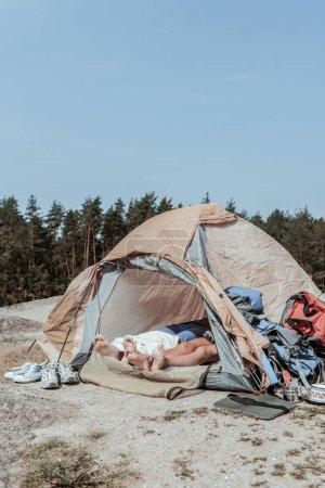Couple de routards pieds nus ayant un peu de repos tout en étant couché dans une grande tente