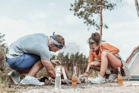 Deux routards allumant un feu de camp près de leur tente pendant le pique-nique